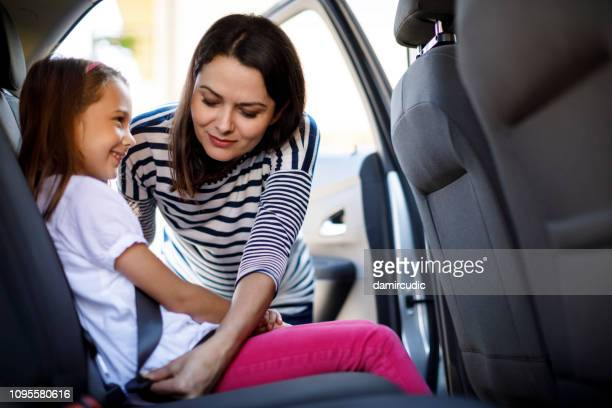 mother fastening child safety seat belt in the car - fastening stock pictures, royalty-free photos & images