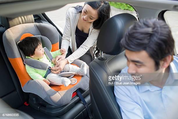 Mother fastening seat belt for daughter