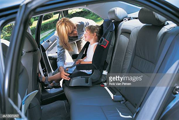 Mother Fastening Seatbelt Over Daughter in Car Seat