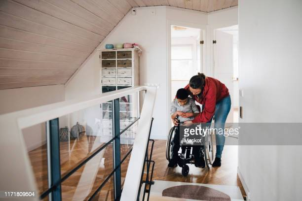 mother fastening wheelchair buckle for disabled son at home - differing abilities fotografías e imágenes de stock