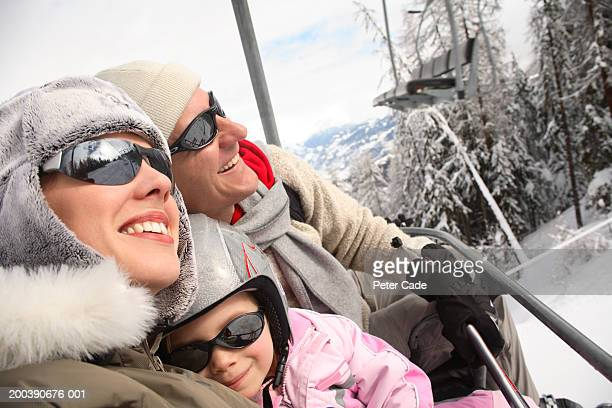mother, father and daughter (3-5) riding ski lift, portrait