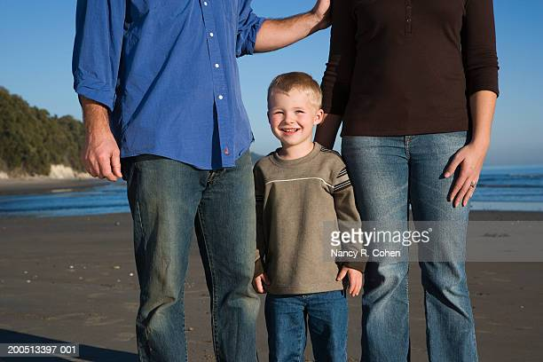 mother, father and son (2-4) standing on beach at sunset - femme entre deux hommes photos et images de collection