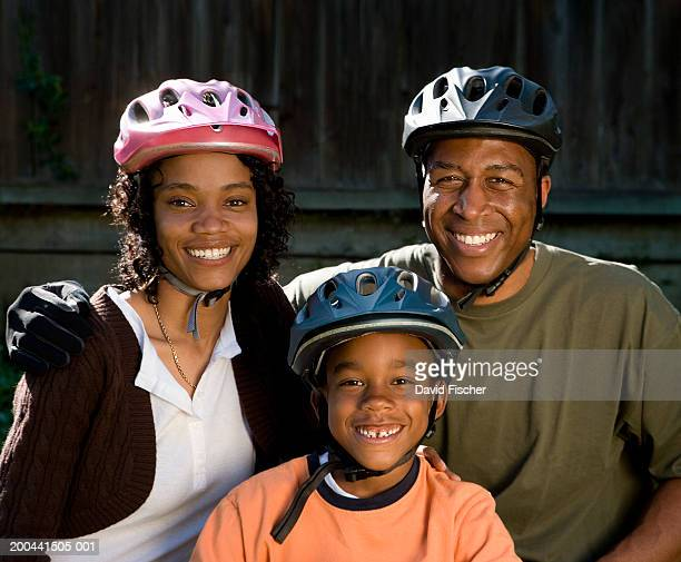 Mother, father and son (6-8) wearing bicycle helmets, portrait