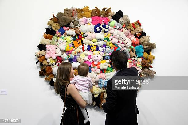 A mother father and their daughter look at the artwork of the artist Mike Kelley No Title which is made of stuffed animals during the VIP opening day...