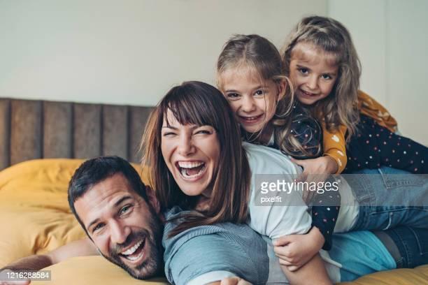 mutter, vater und zwillingsmädchen übereinander gestapelt - familie stock-fotos und bilder