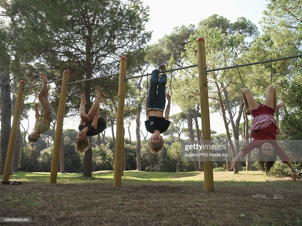 Mother Father And Two Children Hanging Upside Down From Bars Photo