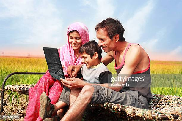 Mother & Father using Laptop with their little son