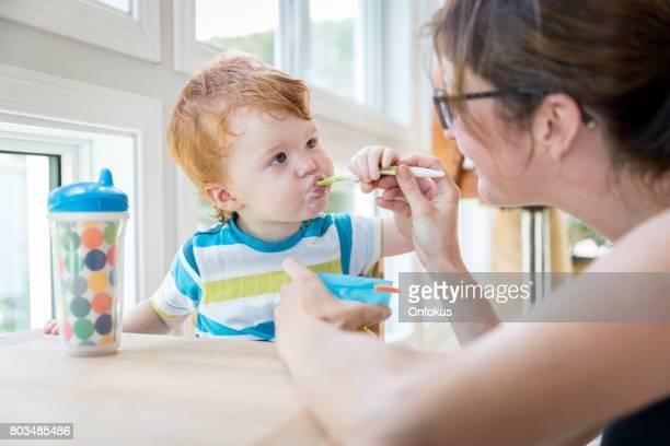 Mother Feeding Baby Boy with Yogurt