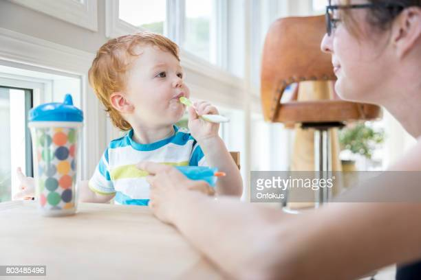 Mother Feeding Baby Boy with Yogurt