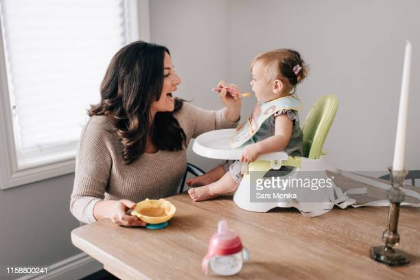 mother feeding baby daughter in child seat on kitchen table - alimentar fotografías e imágenes de stock