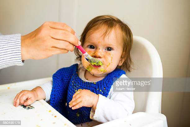 Mother feeding baby girl in high chair