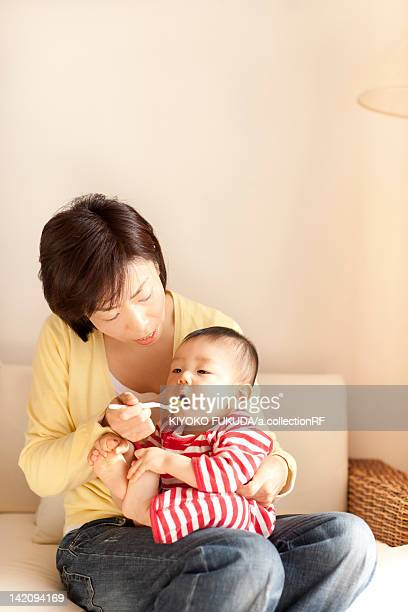 Mother feeding baby girl with spoon