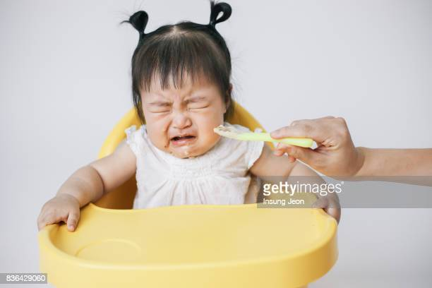 mother feeding baby girl with spoon - first occurrence fotografías e imágenes de stock