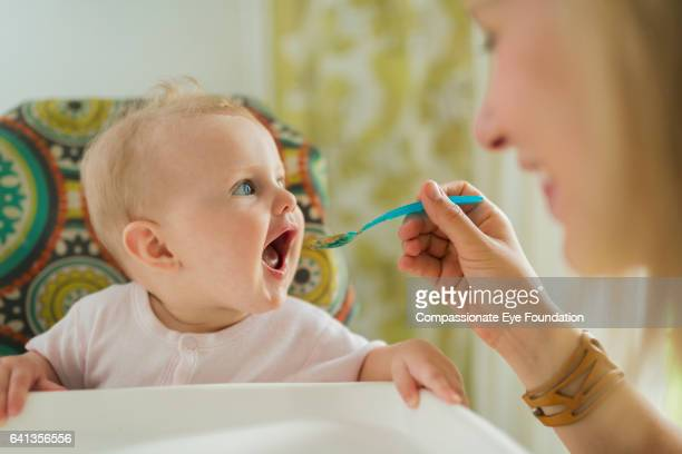 Mother feeding baby in high chair with plastic spoon