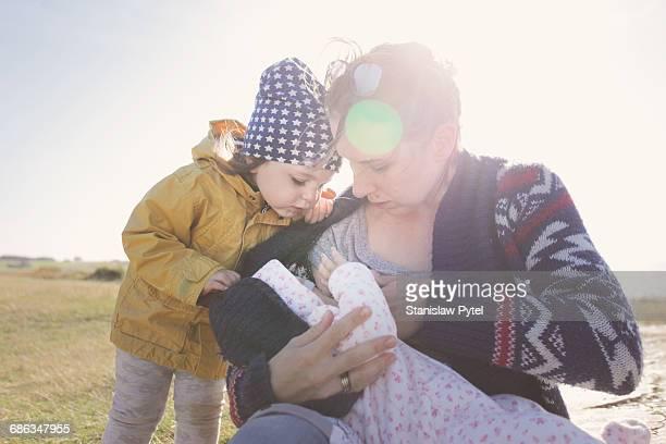 Mother feeding baby, older kid looking