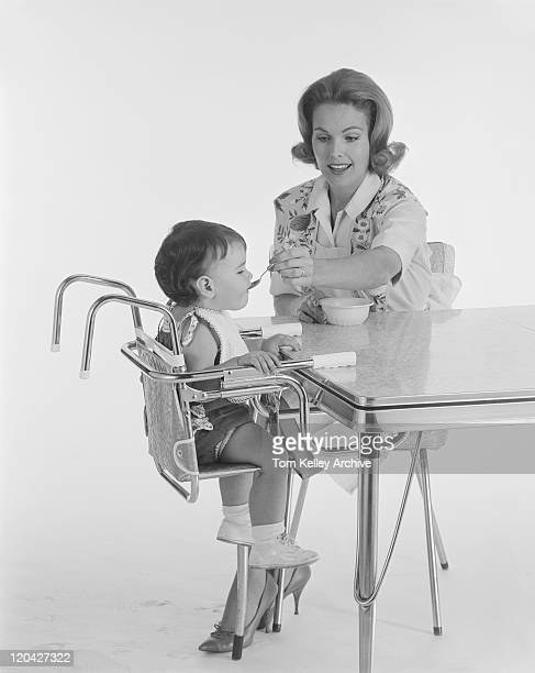 Mother feeding baby on high chair