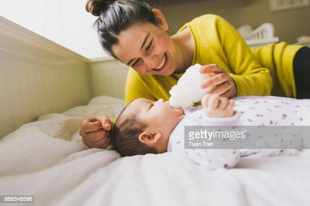 mother feeding baby with bottle - baby bottle stock pictures, royalty-free photos & images