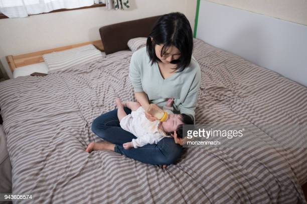 Mother feeding baby with milk