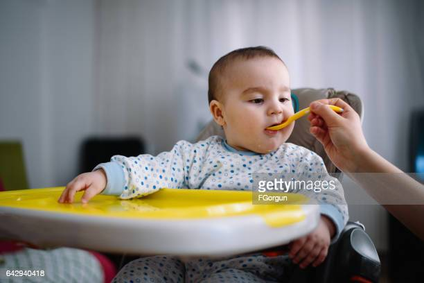 Mother feeding baby with soup