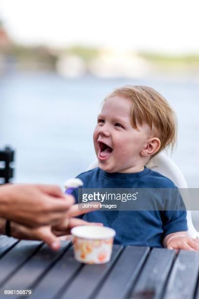 Mother feeding boy outdoors