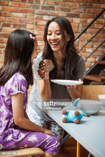 mother feeding cup cake to daughter while sitting at table - one parent stock pictures, royalty-free photos & images
