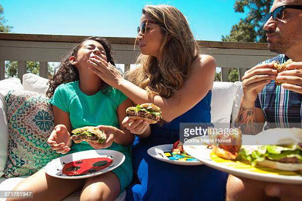 Mother feeding daughter barbecue food in garden