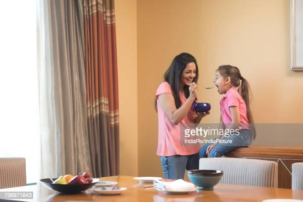 Mother feeding daughter breakfast in dinning room