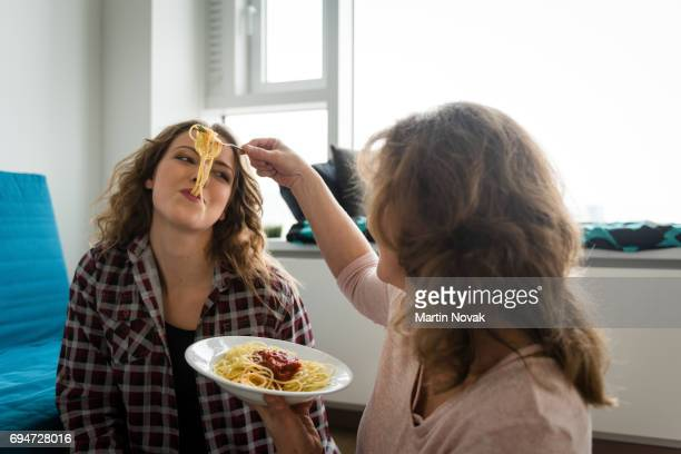 Mother feeding daughter with spaghetti