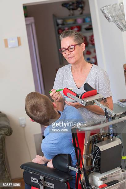 Mother feeding disabled son