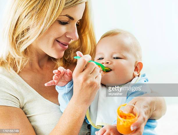 mother feeding her baby. - pureed stock photos and pictures