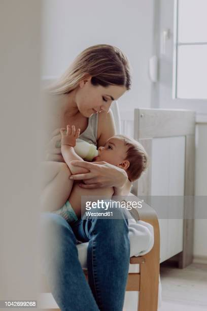 mother feeding her baby son - baby bottle stock pictures, royalty-free photos & images