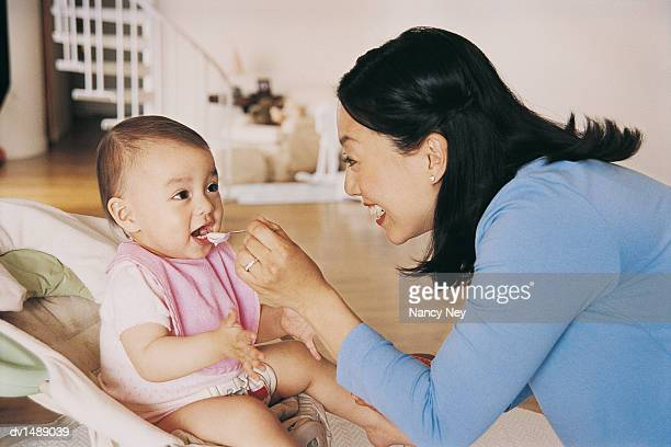 Mother Feeding Her Baby With a Spoon