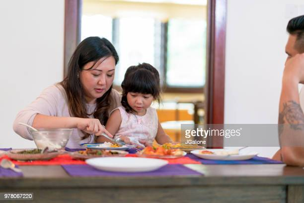 Mother feeding her daughter at the dinner table