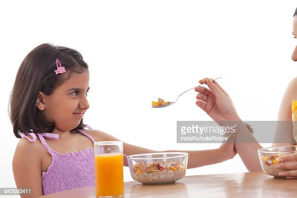 Mother feeding her daughter breakfast