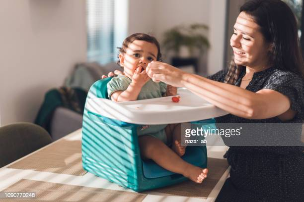 Mother feeding her daughter.