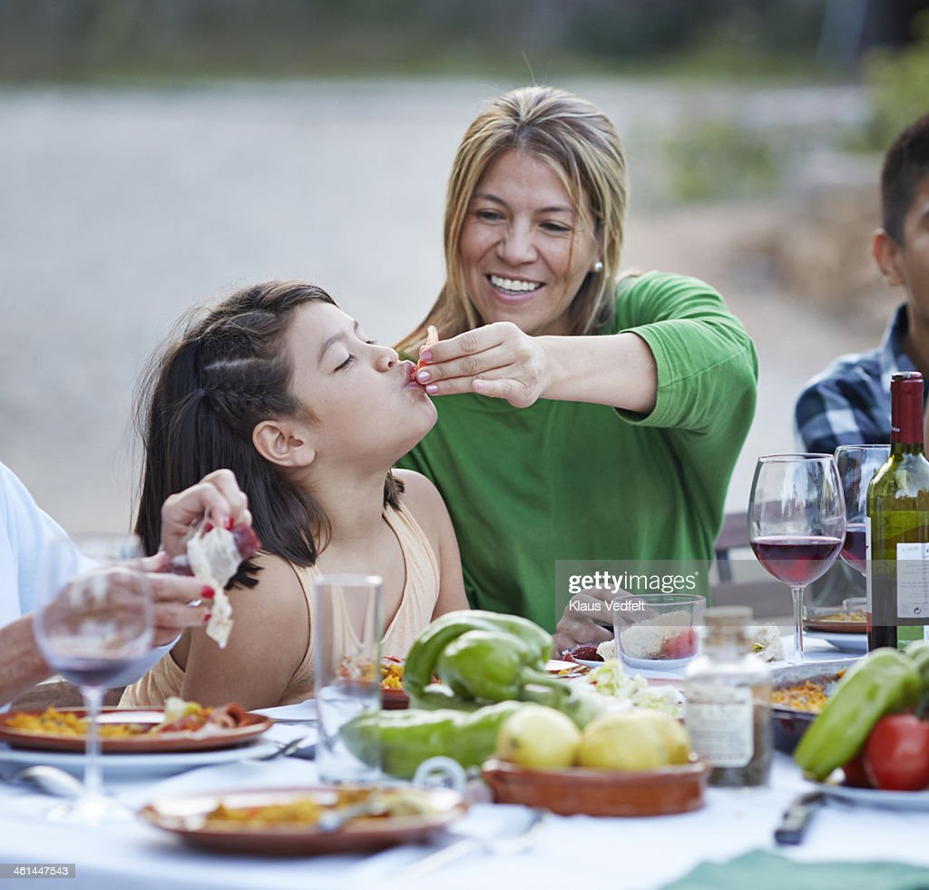 Mother feeding her daughter with tomato at dinner : Stock Photo