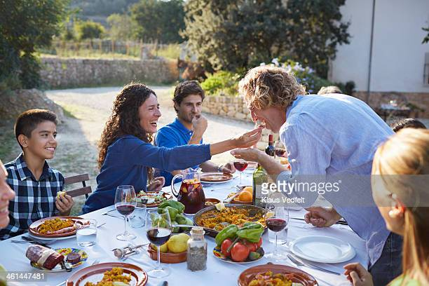 mother feeding her husband at family dinner - klaus vedfelt mallorca stock pictures, royalty-free photos & images