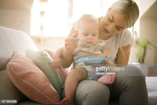 madre alimentando a su niño pequeño en casa. de cerca. - alimentar fotografías e imágenes de stock