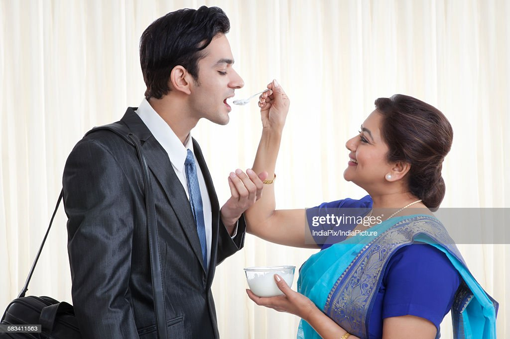 Mother feeding her son dahi : Stock Photo