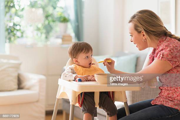 Mother feeding little boy (2-3 years) in high chair