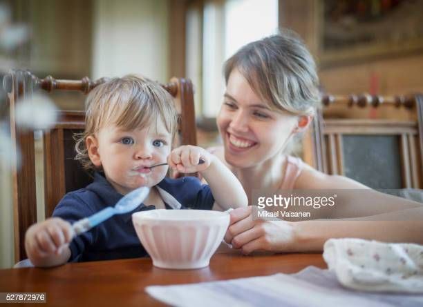 mother feeding little son (12-23 months) - 12 23 months stock pictures, royalty-free photos & images