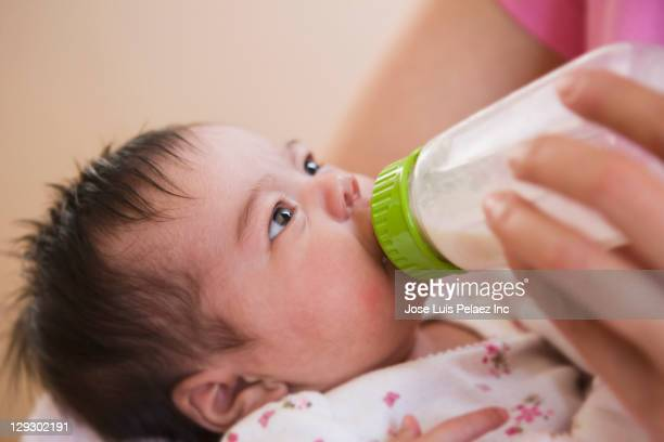 Mother feeding newborn baby daughter