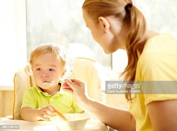 Mother Feeding Son At Home