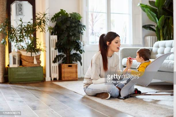 mother feeding son while sitting at home - disabilitycollection stock-fotos und bilder