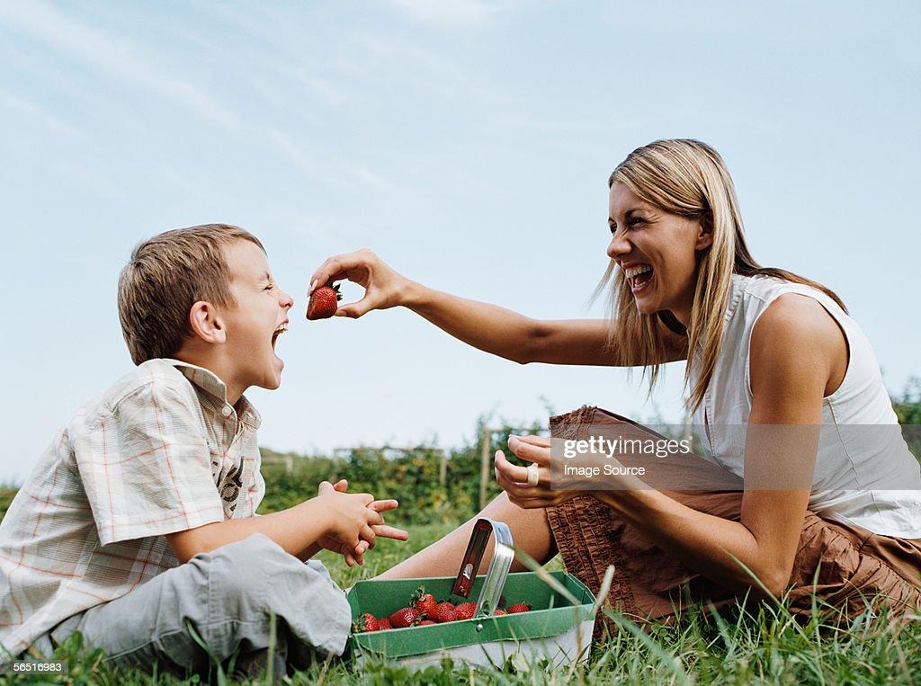 Mother feeding strawberry to son : Stock Photo