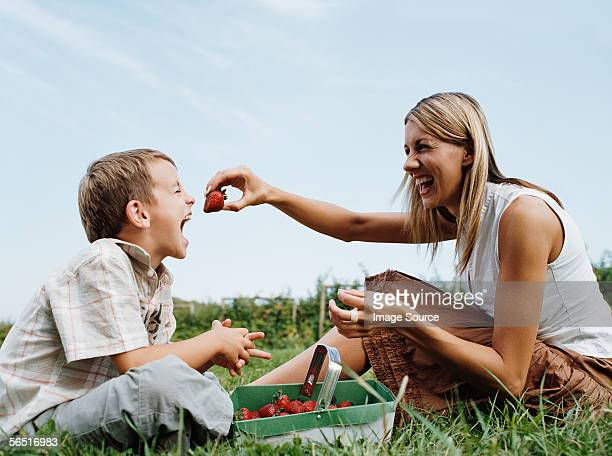 Mother feeding strawberry to son