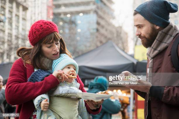 mother feeds baby while father looks on , standing in street market