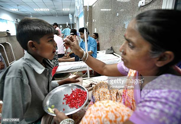 A mother feeds her ailing son as he awaits for routine checkup inside a dengue ward of a Lal Bahadur Shastri hospital on September 19 2015 in New...