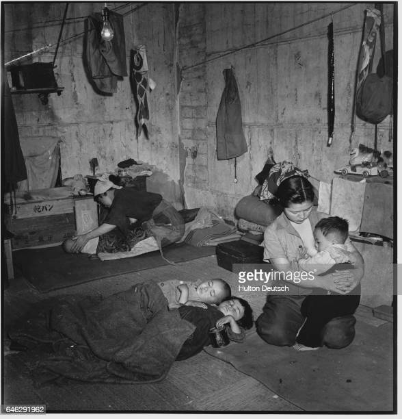 A mother feeds her baby while two youngsters lie sleeping in a disused garage on the outskirts of Tokyo