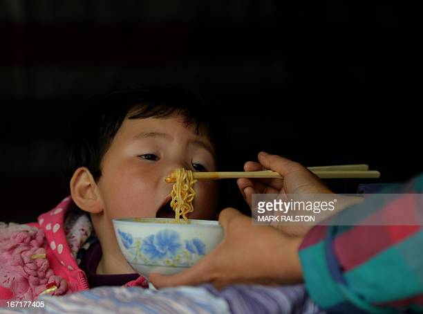 A mother feeds her child as they stay in a temporary shelter after a magnitude 70 earthquake hit Lushan Sichuan Province on April 22 2013 Clogged...
